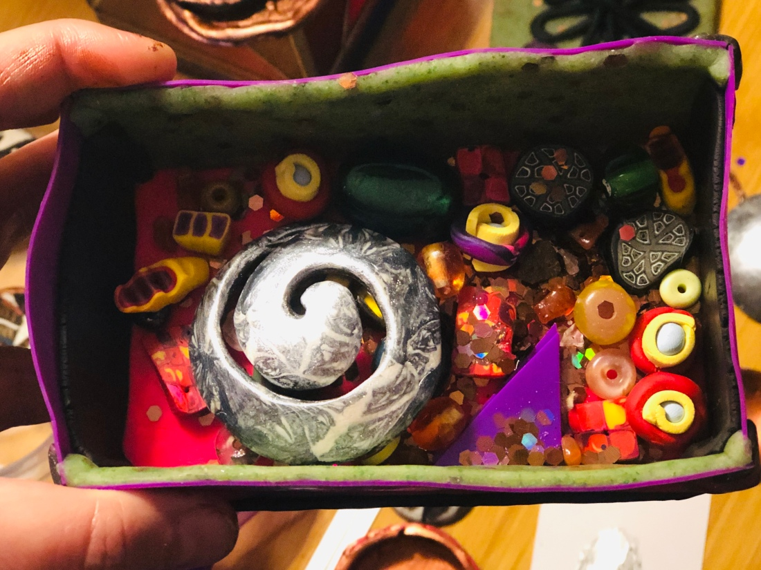 various polymer clay beads in a box